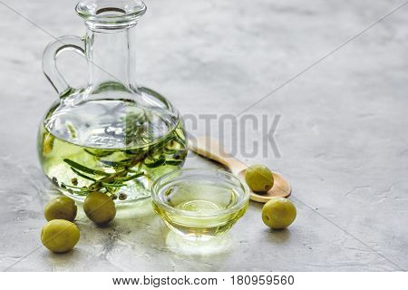 extra oil in carafe with spices and fresh olive on stone desk background mock-up