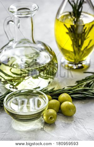 natural oils concept with fresh olives and glass jar on stone table background