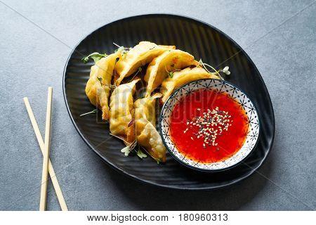 Steamed gyozas with teriyaki sauce and sesame seeds