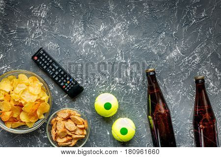 snacks for watching sport match with balls and beer on dark desk background top view mock-up