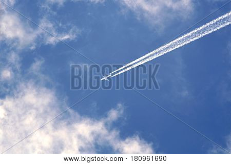 Big passenger supersonic planewith two jet engines flying high in blue sky with white clouds and leaving long white trace