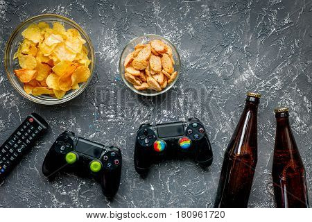 snacks for playing video games with joypad and beer on dark desk background top view mock-up