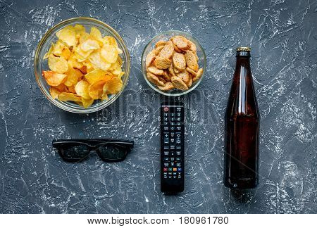 snacks for watching TV film with glasses and control on dark desk background top view