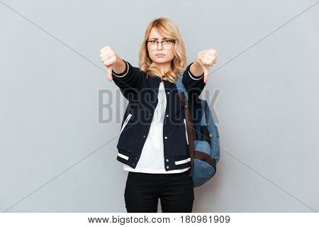 Photo of sad young lady student wearing glasses with backpack posing over grey wall. Looking at camera showing thumbs down.