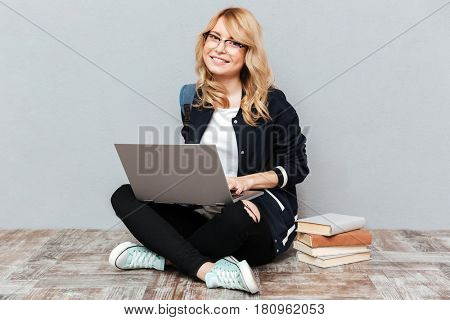 Picture of smiling young woman student wearing glasses with backpack posing over grey wall. Looking at camera using laptop computer.
