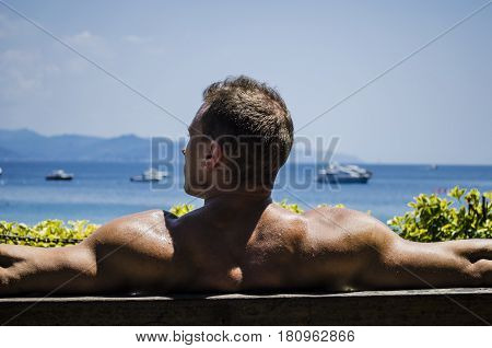 Muscular Shirtless Hunk Man Outdoor at Seaside Looking at the Sea, Seen from the Back, Sitting on Bench under the Sun