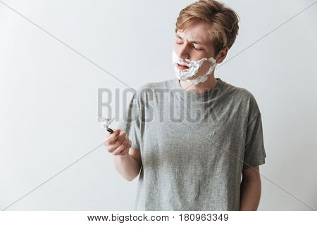 Displeased man in t-shirt shaving foam holding razor over gray background