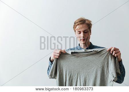 Young man in jeans shirt holding t-shirt over gray background