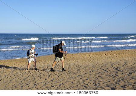 Nordic Walking - senior couple walking along sea.
