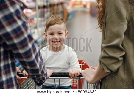 Young boy sitting on shopping trolley and looking at the camera while your parents pushing a trolley