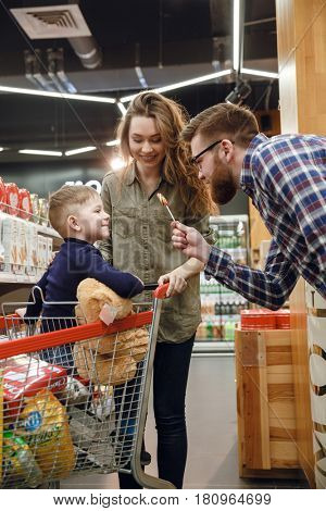 Vertical image of a father giving candy to his son which sitting in shopping trolley in supermarket while mother standing near them