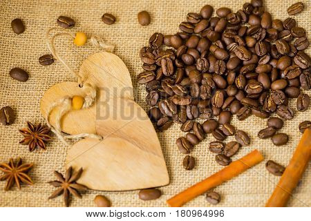 Grains of roasted coffee on sackcloth background with decorative wooden hearts. Coffee background for creative concepts for any day or advertising with copy space. Coffee break concept.