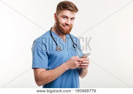 Portrait of male doctor texting, loooking at camera and smiling while standing against white background.