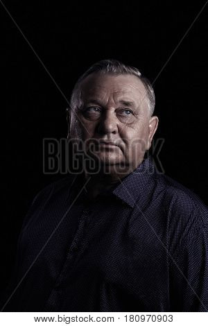 Classic portrait of aged man wearing shirt against black background - retirement concept