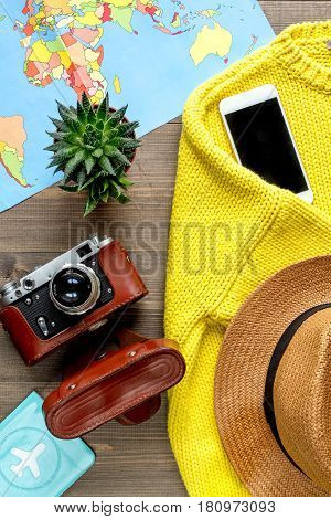 vacation concept with traveller outfit clothes, mobile, world map and camera on wooden desk background top view