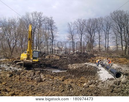 The workers cover the culvert with waterproofing. Nearby there is an excavator.
