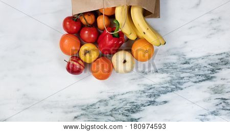 Flat lay view of fruits and vegetables spilling out of a paper bag onto marble stone countertop