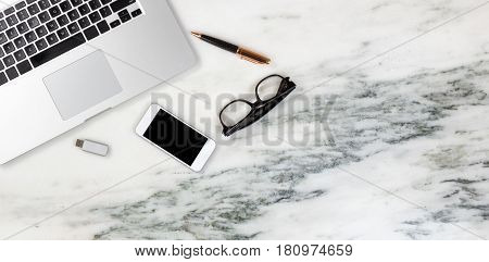 Flat lay of a partial laptop pen and reading glasses smartphone thumb drive on natural marble desktop