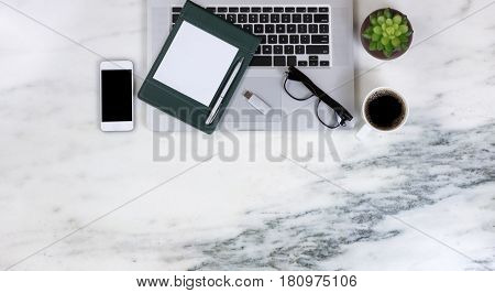 Flat lay of a partial laptop plant smartphone pen paper reading glasses thumb drive and dark coffee on natural marble desktop