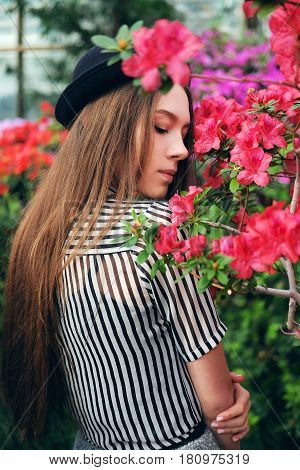 Tender sweet young woman with long chestnut hair and black hat enjoying azalea flowers in greenhouse. Romantic mood concept.
