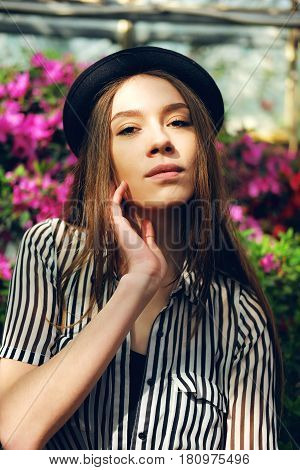 Sensual tanned woman in tropical garden near azalea bushes hiding from the sunlight