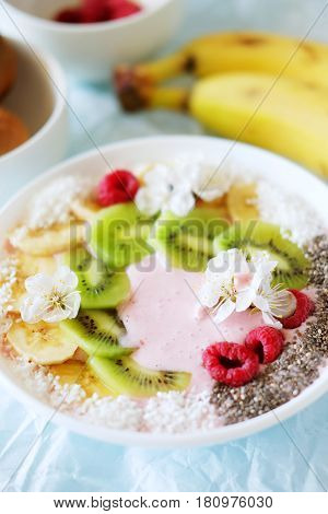 Raspberry and banana smoothie bowl with kiwi slices shredded coconut and chia seeds. Healthy food concept.