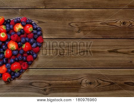 Colorful heart shape made using various berries including strawberries raspberries and blue berries on a wooden background with space for text.