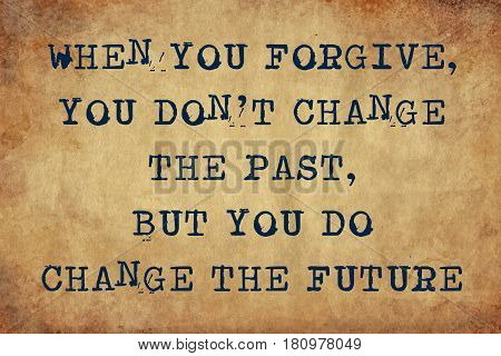 Inspiring motivation quote of when you forgive, you don't change the past, but you do change the future with typewriter text. Distressed Old Paper with Typing image.