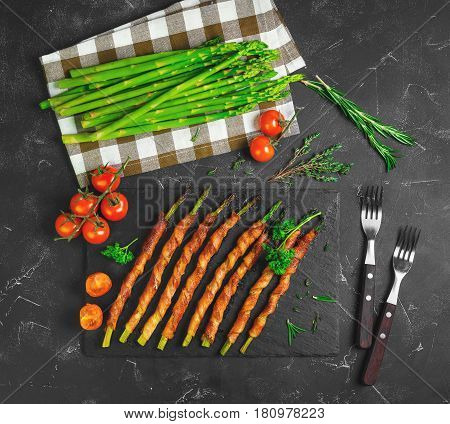 Asparagus baked grill wrapped in bacon. Ingredients for asparagus wrapped in bacon cherry tomatoes parsley thyme rosemary fresh asparagus. Dark black background. Top view from above and copy space.