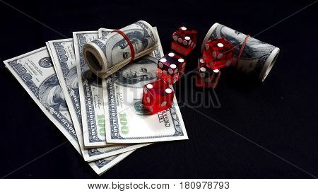 Five red dice and banknotes on black fabric copy space Gambling devices concept