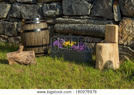 Oak Wine Barrel, Handcrafted Wood Stool, Pot Of Violets And Bell Flowers With A Natural Wall Of Rock