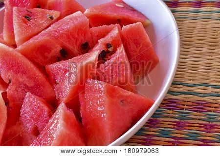 Close up of chopped red watermelon in white plate put on local mat fresh fruit