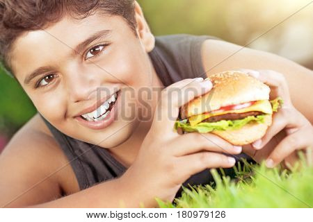 Closeup portrait of a cute happy teen boy lying down on green grass and eating delicious burger, enjoying tasty lunch on sunny day, happy time at summer camp