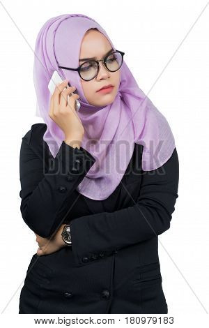 Beautiful modern Young Asian Muslim business woman holding a white cell phone and she is seriousisolated on white background.
