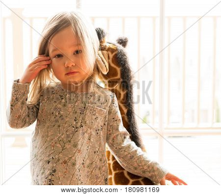 Young caucasian female toddler looking seriously at the camera with strong backlighting