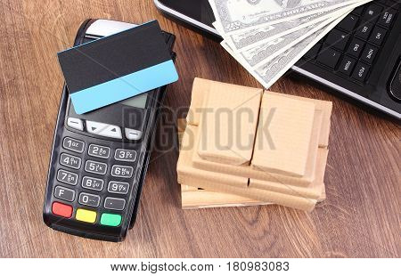 Payment Terminal With Credit Card, Currencies Dollar, Laptop And Wrapped Boxes On Wooden Pallet