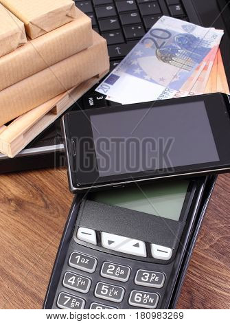 Payment Terminal With Mobile Phone With Nfc Technology, Currencies Euro, Laptop And Wrapped Boxes On