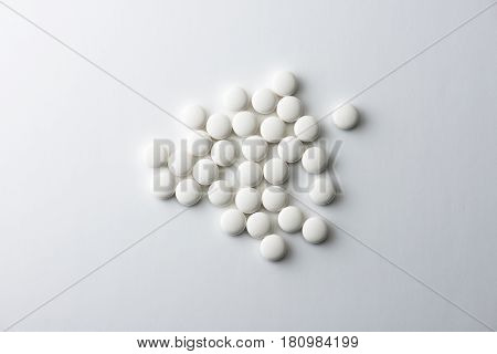 White medicine tablets or pharmaceutical pills isolated on white background, shot from above.