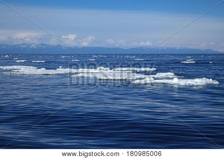 White ice floating on blue water surface