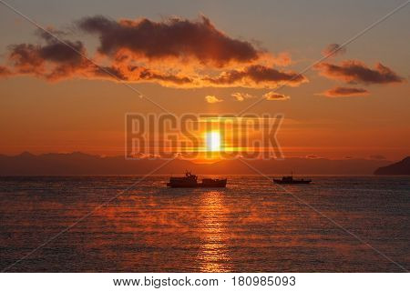 Two ships floating on background of red sunset
