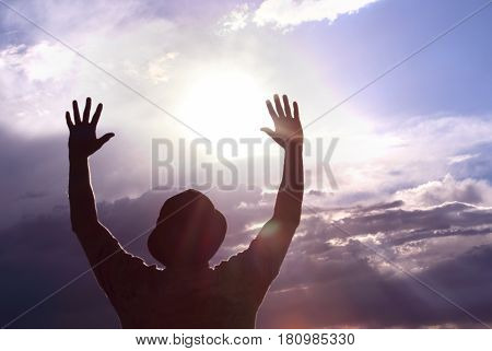 Men welcoming sunrise with raised hands concept of Freedom and Inspiration