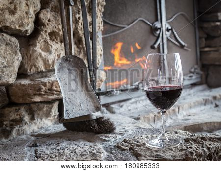 horizontal image of a glass of red wine sitting on the hearth with the fire burning in an old rustic stone fire place.