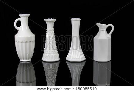 Four elegant white vases on black background