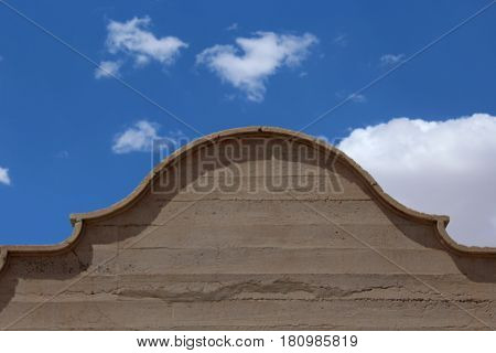 Top of an adobe building with scallloped trim edge against a bright  blue sky and white fluffy clouds