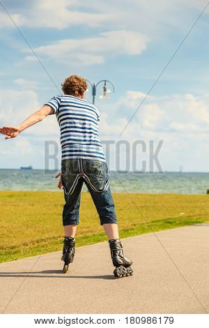 Holidays active lifestyle freedom concept. Young fit man on roller skates riding outdoors on sea coast guy rollerblading on sunny day