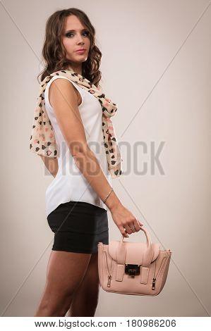 Elegant outfit. Female fashion. Girl in fashionable clothes holding bag handbag studio shot on gray background