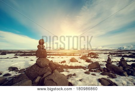 Stone stacked balance in winter landscape, with bright sunlight