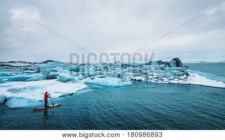 Beautiful view of icebergs glacier lagoon with a guy paddle boarding (sup), global warming and climate change concept