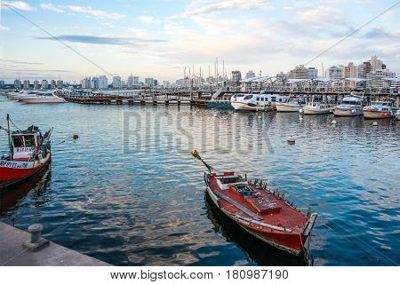 Maldonado April 4 2017 - Classic Red Fishing Boat moored in front of the yachts of the rich people in Punta del Este harbor Uruguay