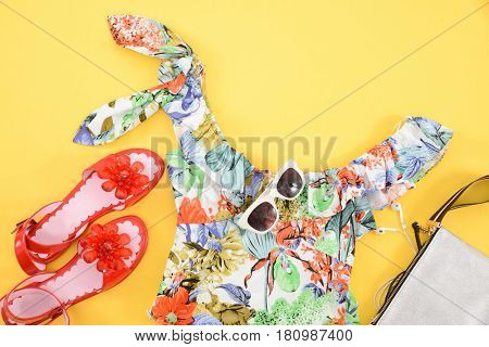 Fashion. Summer woman accessories-Summer floral clothes,sunglasses, shoes ,bag on yellow background